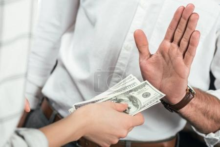 cropped view of businessman refusing to take bribe from partner, isolated on black