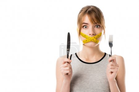 Photo for Shocked young woman with measuring tape tied around her mouth holding fork and knife isolated on white - Royalty Free Image