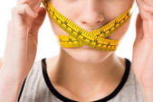 cropped shot of woman with measuring tape tied around her mouth touching head isolated on white