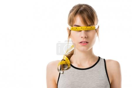young slim woman with measuring tape tied around her eyes isolated on white