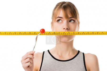 young woman with measuring tape in front her mouth trying to eat fresh tomato isolated on white