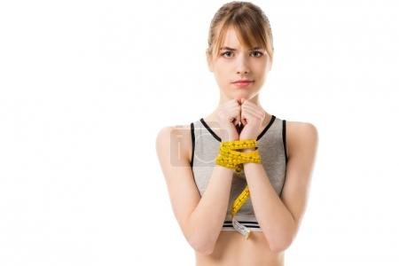 young slim woman with hands tied in measuring tape isolated on white