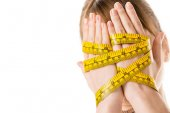 close-up shot of woman covering face with hands tied in measuring tape isolated on white