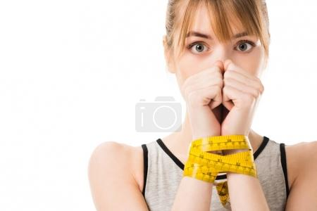 scared young woman covering face with hands tied in measuring tape isolated on white