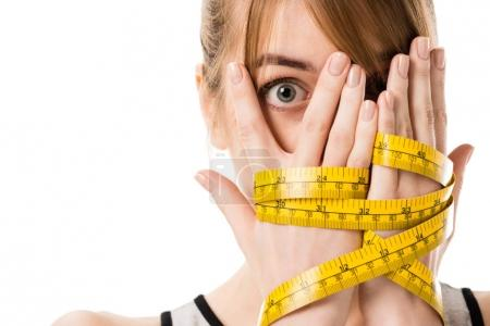 shocked young woman covering face with hands tied in measuring tape isolated on white