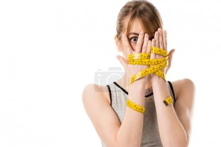 frightened young woman covering face with hands tied in measuring tape isolated on white