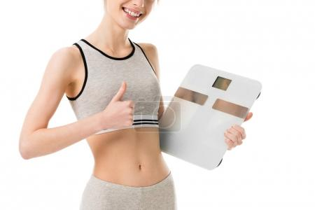cropped shot of happy slim woman holding scales and showing thumb up isolated on white