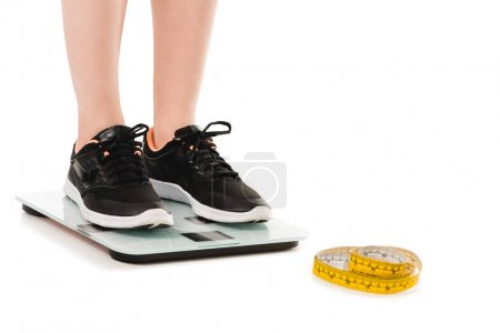 cropped shot of woman standing on scales with measuring tape lying on floor isolated on white