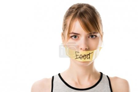 Photo for Woman with stiker with striked through word food covering mouth isolated on white - Royalty Free Image