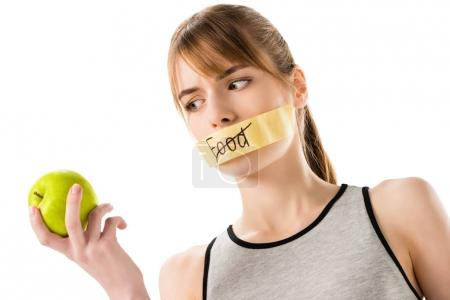 young woman with stick tape with striked through word food covering mouth looking at apple in hand isolated on white
