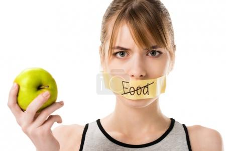 Photo for Young woman with stick tape with striked through word food covering mouth holding apple isolated on white - Royalty Free Image