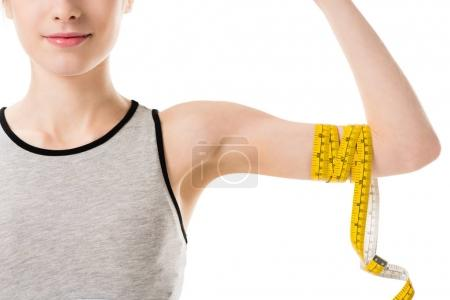 cropped shot of young woman showing her biceps tied with measuring tape isolated on white