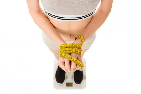 cropped shot of young woman with hands tied with measuring tape standing on scales isolated on white