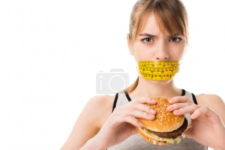 young woman with mouth tied in measuring tape holding burger isolated on white