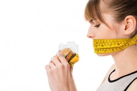 Photo for Woman with mouth tied in measuring tape trying to eat burger isolated on white - Royalty Free Image