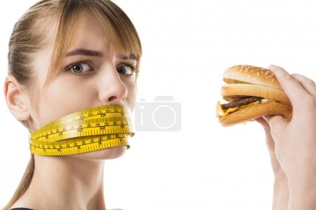 young woman with mouth tied in measuring tape trying to eat burger isolated on white
