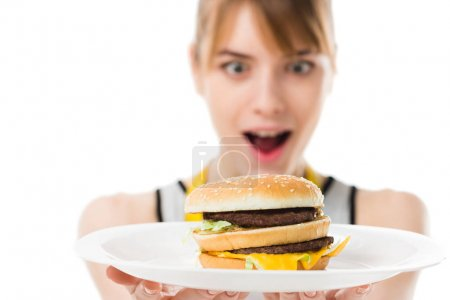 excited young woman looking at burger on plate isolated on white
