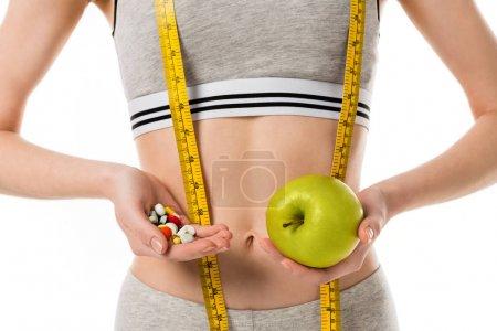 Photo pour Plan recadré de femme mince tenant pomme fraîche et pilules isolées sur blanc - image libre de droit