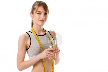 young slim woman wih measuring tape holding glass of water isolated on white