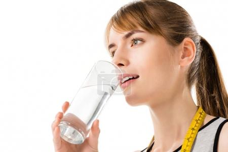 Photo for Young woman with measuring tape on neck drinking water isolated on white - Royalty Free Image