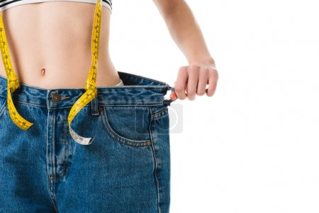 Photo for Cropped shot of slim woman with measuring tape in oversized jeans isolated on white - Royalty Free Image
