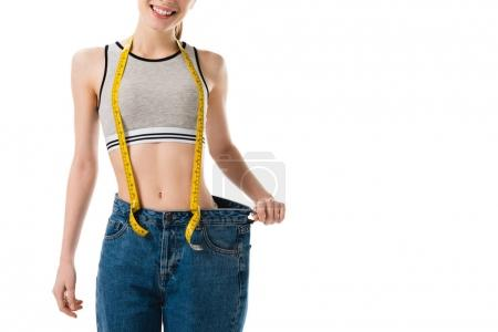 smiling slim woman with measuring tape in oversized jeans isolated on white