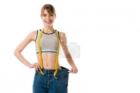 young slim woman with measuring tape in oversized jeans isolated on white