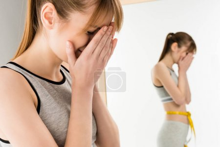 crying woman in front of mirror with measuring tape on waist isolated on white
