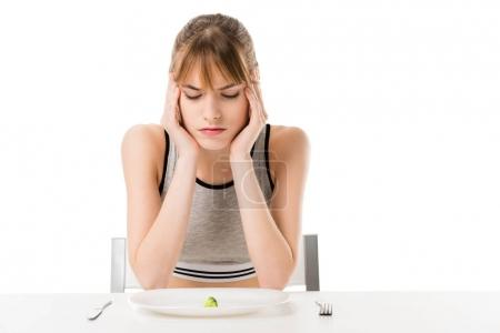disgusted slim woman with piece of broccoli on plate isolated on white