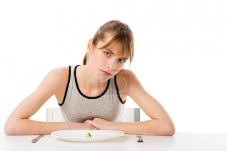 depressed slim woman with piece of broccoli on plate isolated on white