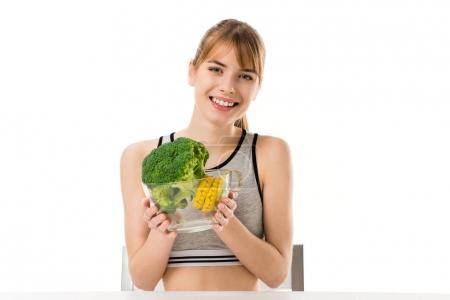 happy slim woman with broccoli covered in measuring tape in bowl isolated on white