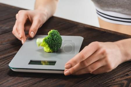 Photo for Cropped shot of woman measuring weight of broccoli - Royalty Free Image