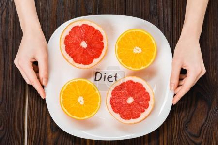 cropped shot of woman holding plate with halved citrus fruits and diet inscription