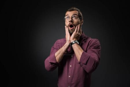 portrait of shocked man in eyeglasses looking away isolated on black