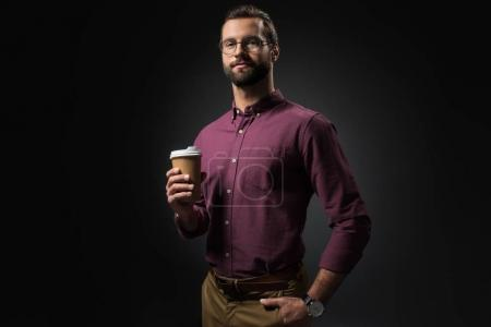 portrait of businessman in eyeglasses with coffee to go isolated on black