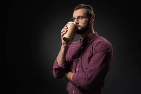 portrait of businessman drinking coffee to go isolated on black