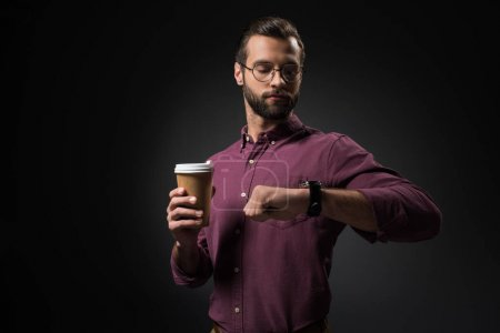 portrait of businessman with coffee to go checking time isolated on black