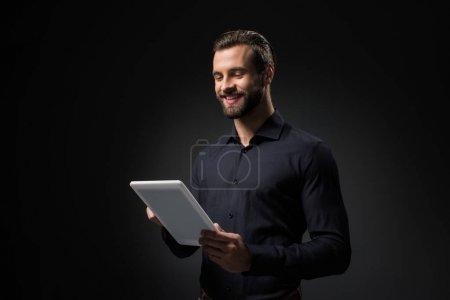 Photo pour Portrait d'homme souriant avec tablette numérique isolé sur noir - image libre de droit