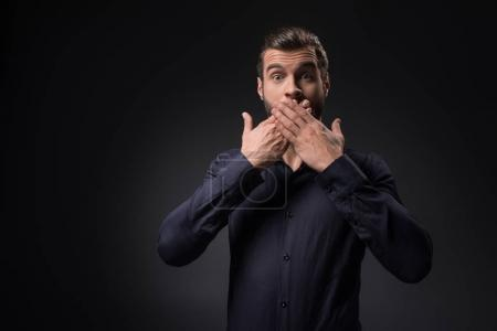 portrait of shocked man covering mouth with hands isolated on black