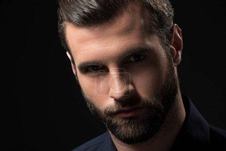 Foto de Retrato del hombre barbudo confiado mirando a cámara aislada en negro - Imagen libre de derechos