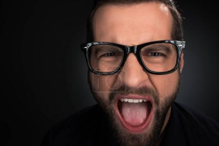portrait of man in eyeglasses screaming isolated on black