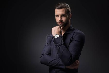 portrait of thoughtful man looking at camera isolated on black