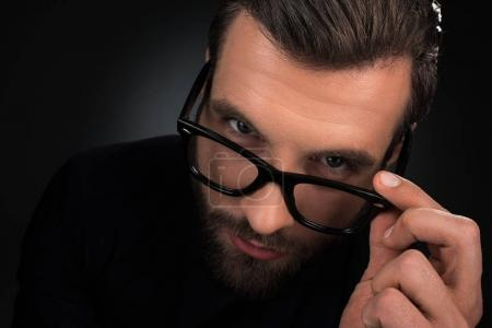 portrait of man in eyeglasses looking at camera isolated on black