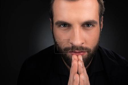 Photo pour Portrait d'un homme regardant la caméra tout en priant isolée sur fond noir - image libre de droit