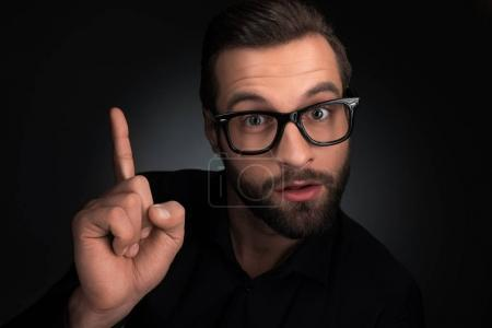 portrait of man in eyeglasses pointing up isolated on black
