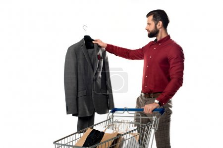 man with shopping cart full of shopping bags looking at jacket in hand isolated on white
