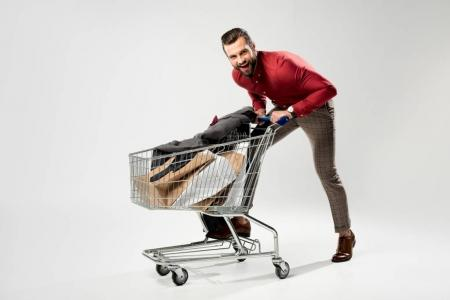 cheerful man with shopping cart full of shopping bags and jacket isolated on grey