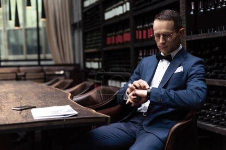 Photo pour Bel homme en costume élégant regardant la montre en attendant la date au restaurant - image libre de droit