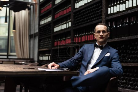 happy handsome man in stylish suit sitting in armchair in front of wine storage