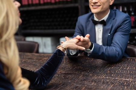 cropped shot of couple having date at restaurant and holding hands